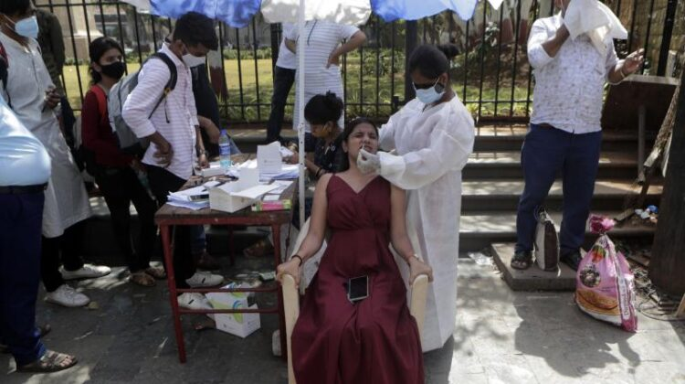 A health worker takes a nasal swab sample to test for COVID-19 near the landmark Gateway of India in Mumbai, on April 2, 2021. (AP/Rajanish Kakade)